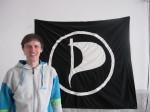 Berliner Piraten-Fraktionschef Andreas Baum vor Piratenfahne (Foto: JH)